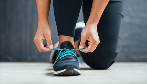 A woman tying her shoes before a gentle jog to reduce back pain.