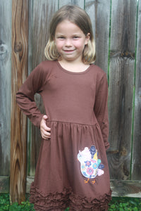 young girl smiles at camera in a brown dress with ruffles and turkey applique