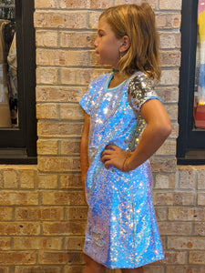 a girl stands in front of a brick wall with hand on hip wearing a sequin dress
