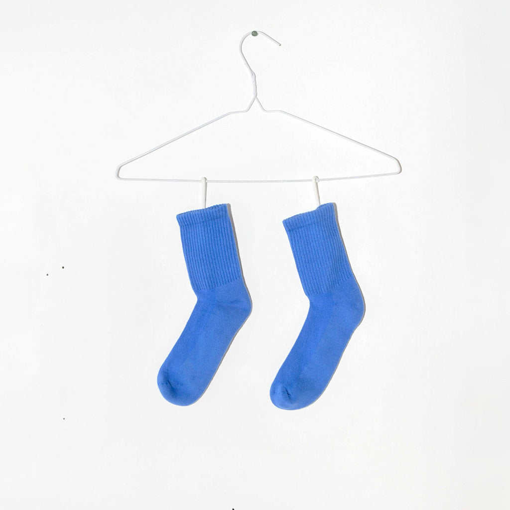 Bright blue socks rest below a wire hanger on a white background.