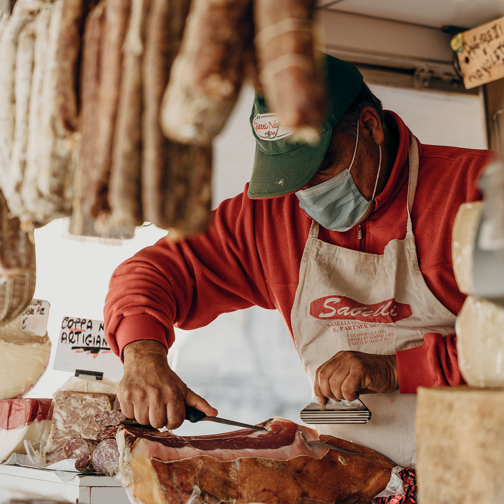 A butcher wearing a surgical mask slices cured meats.