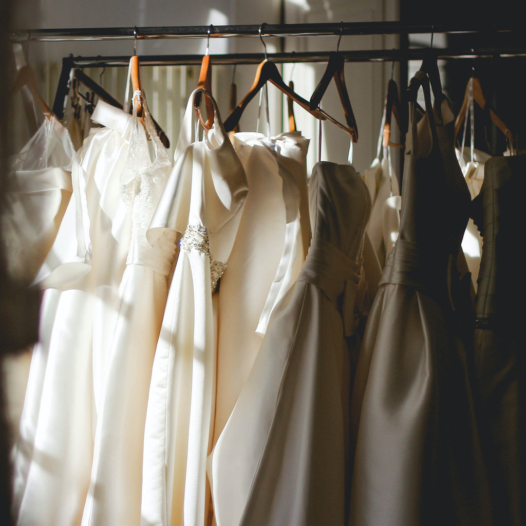 White dresses on wooden hangers in a sun-filled room.