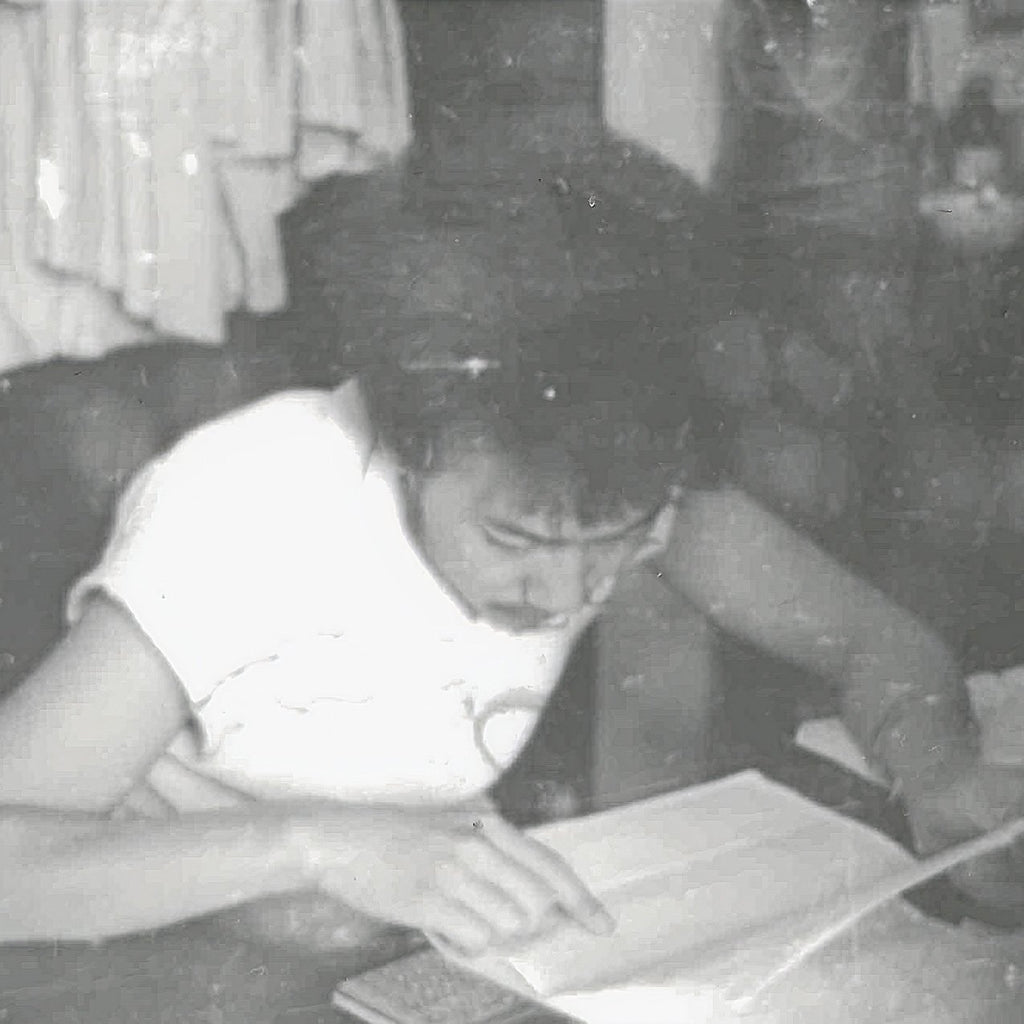 Young Dirty Labs co-founder Dr. Pete studying from a book in an old black and white photograph.