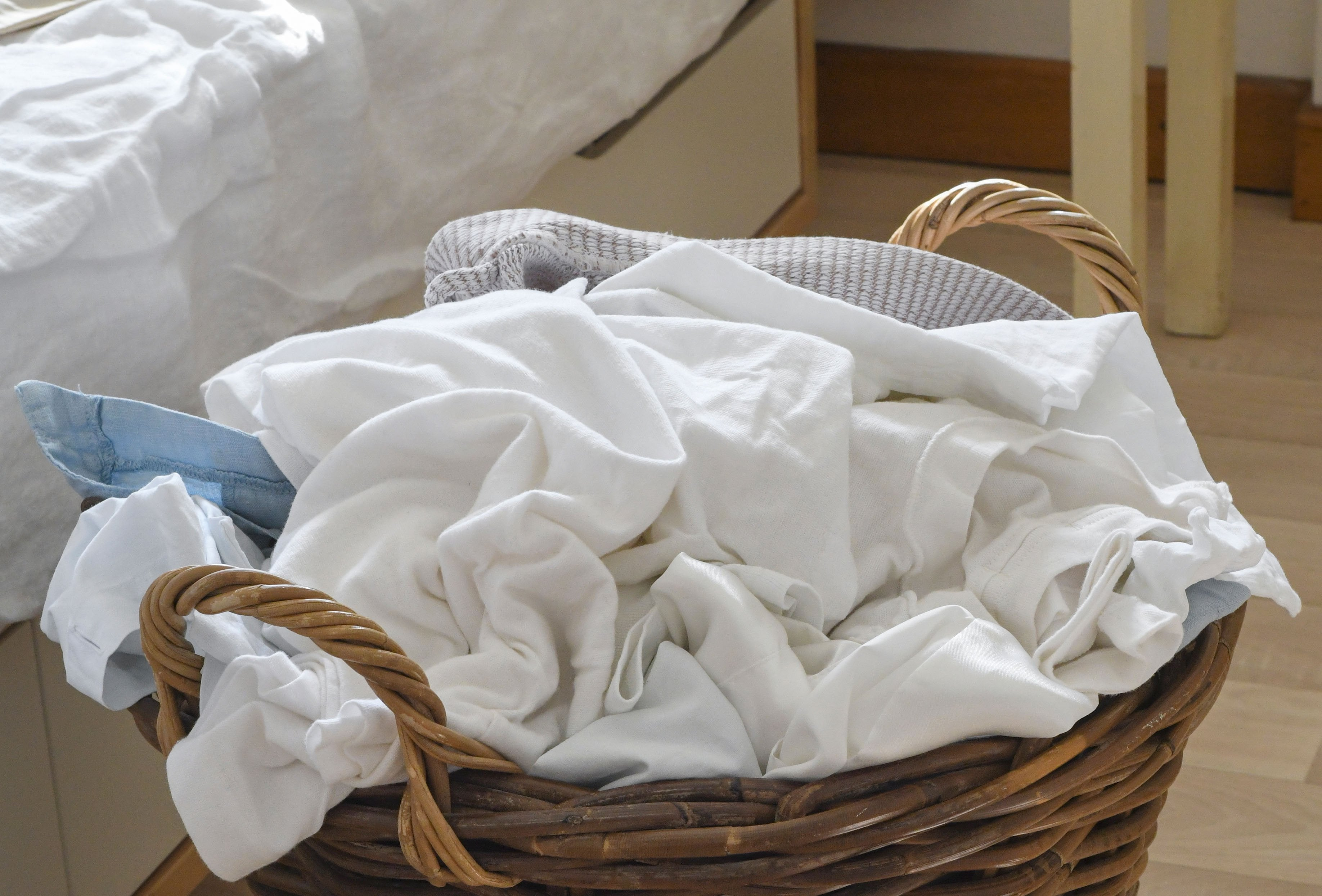 Close up of laundry in a wicker basket on a bedroom floor.