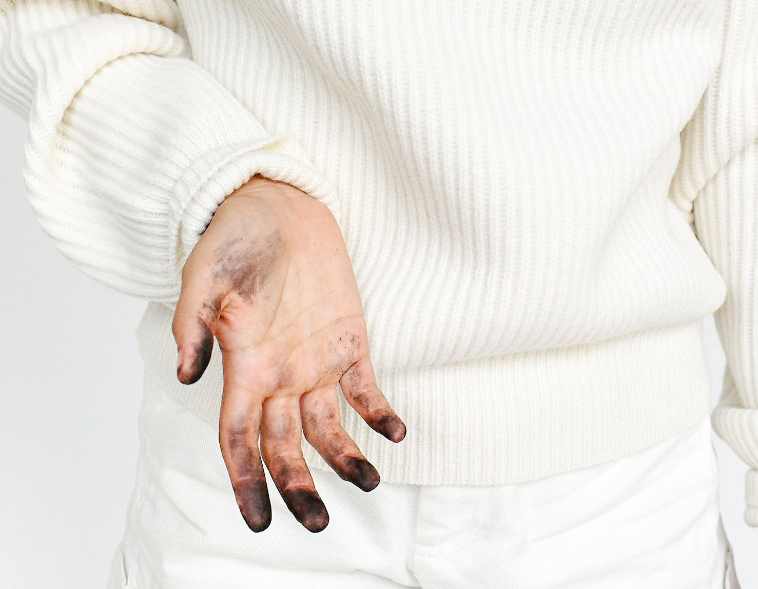 Close up of a person in white clothing revealing dark stains on their hand and fingertips.