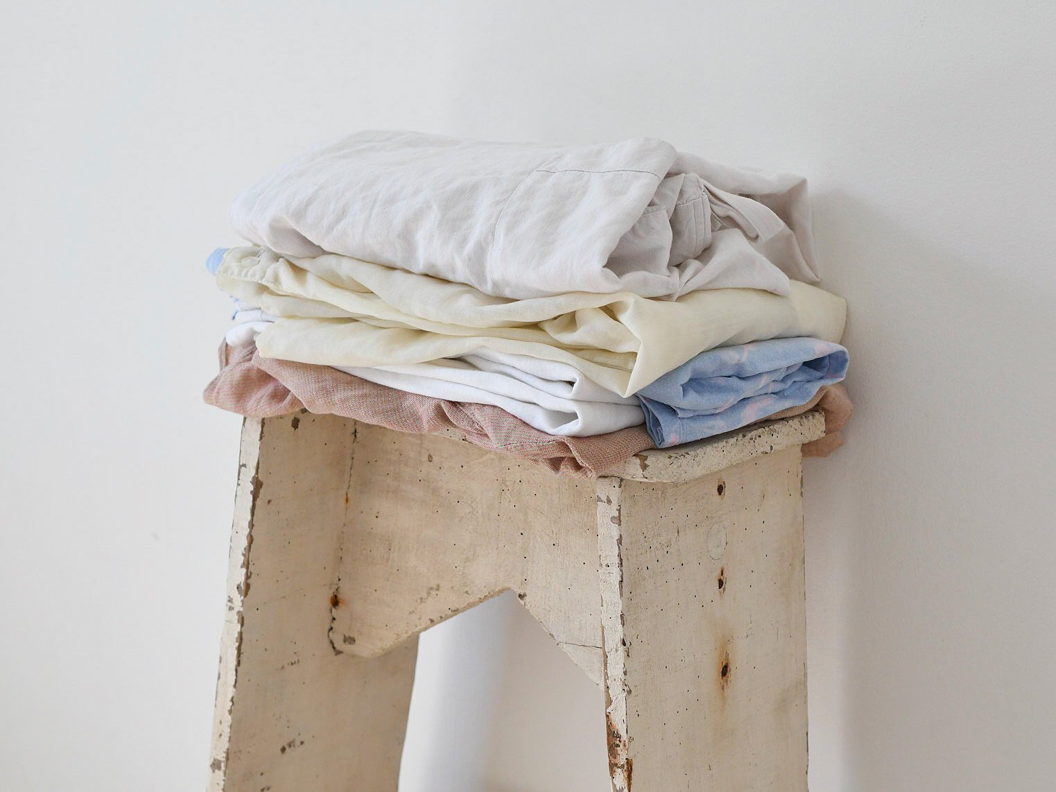 Folded laundry rests on top of a small weathered ladder leaning against a white wall.