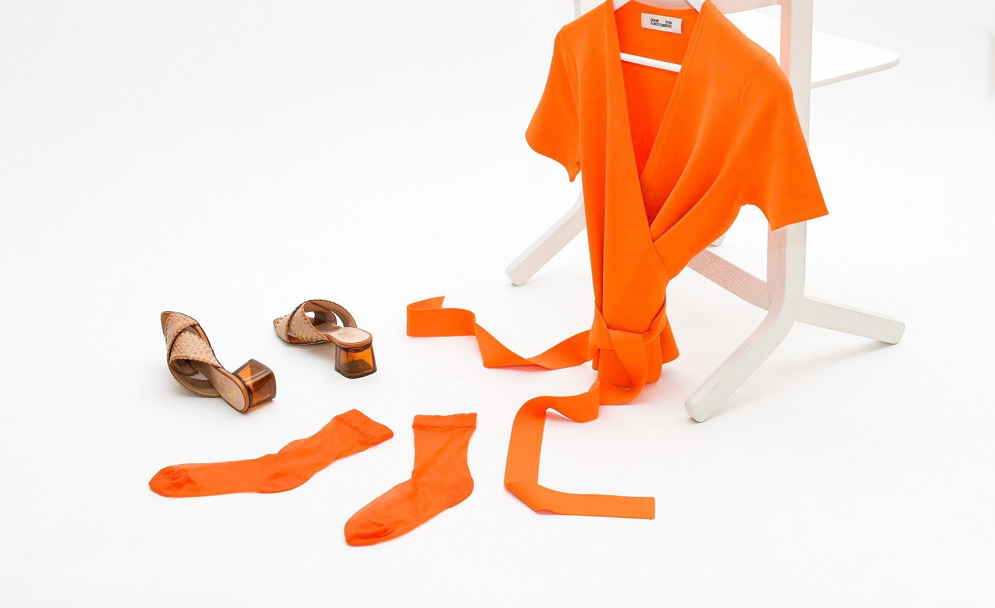 Orange dress and socks on a white chair on a white background next to high heeled shoes.