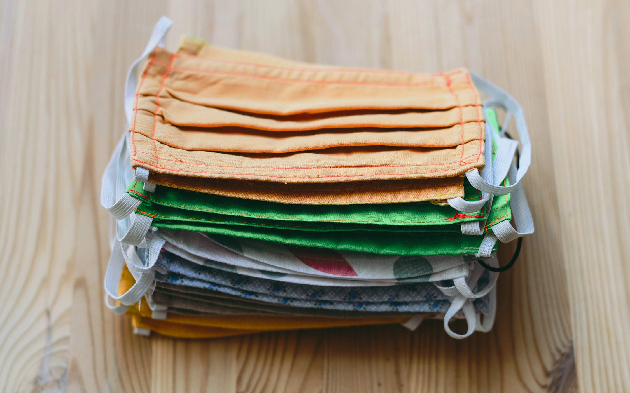 A stack of cloth face masks on a wooden table.
