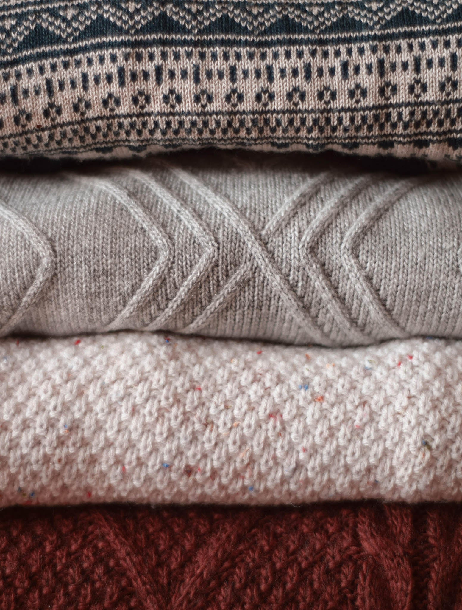 Folded stack of knit sweaters