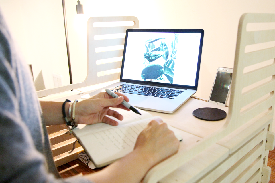 Person standing at a wooden standing desk writing with a laptop