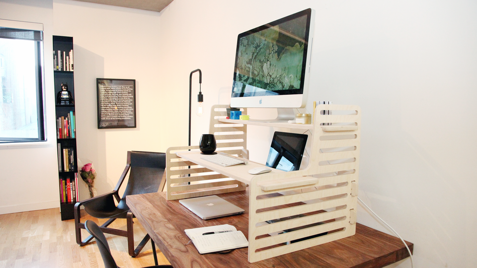 Adjustable standing desk in a nice office with one monitor