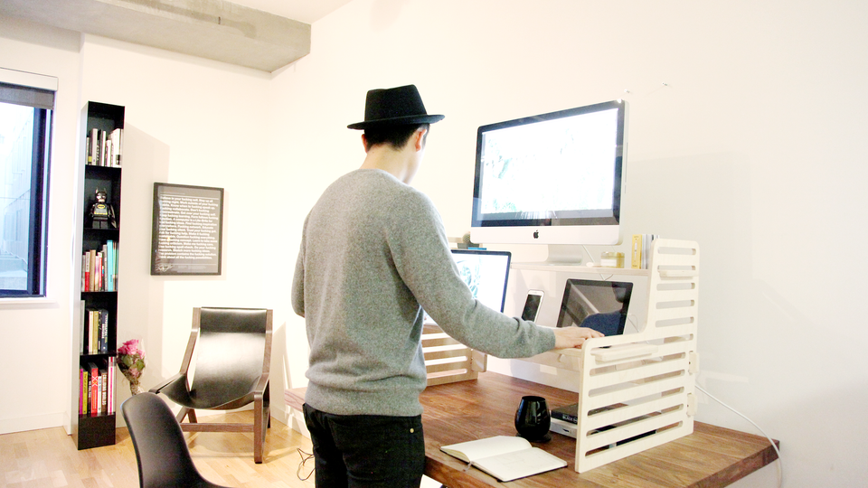 Person standing up using a wooden standing desk converter with nice office furniture