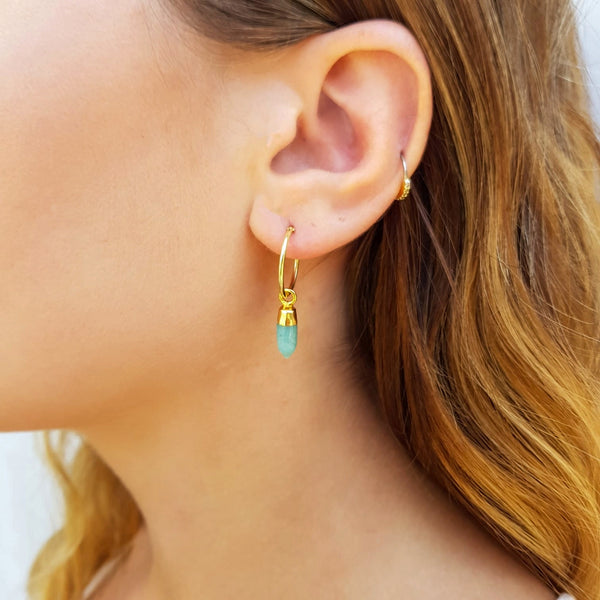 Model wearing gold hoop earrings with an amazonite drop pendant.