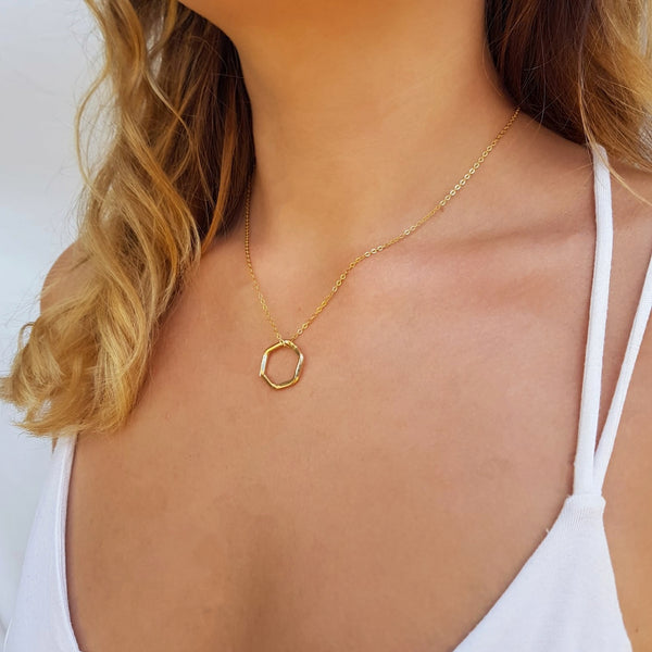 Gold necklace with hexagon pendant.