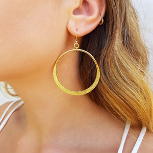 Model wearing large gold hoops with textured finish.