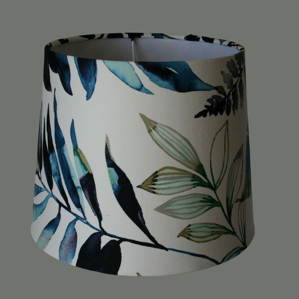 Glass bottle table lamp with blue feather and fern fabric shade