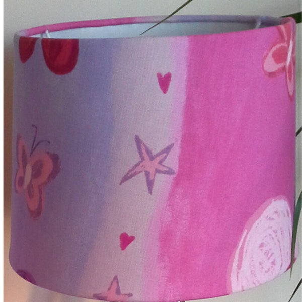 Stars and hearts alternate with flowers and butterflies on this pretty pink fabric. Close up.