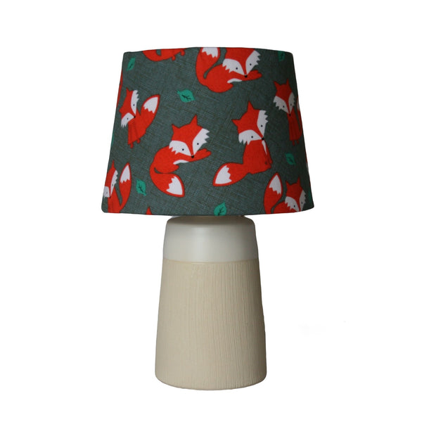 Orange foxes on a small lampshade with a small cream and white light stand.