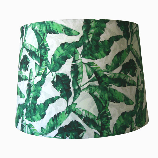Green banana leaves fabric on a large tapered lampshade.
