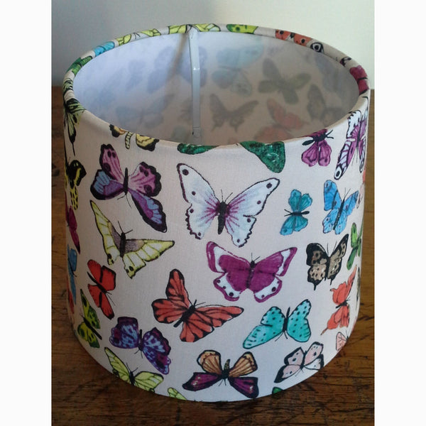 Multicoloured butterflies on cream background fabric on a small lampshade.