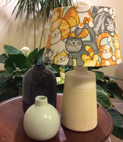 Unlit picture of small table lamp with lots of cats, in various colours.