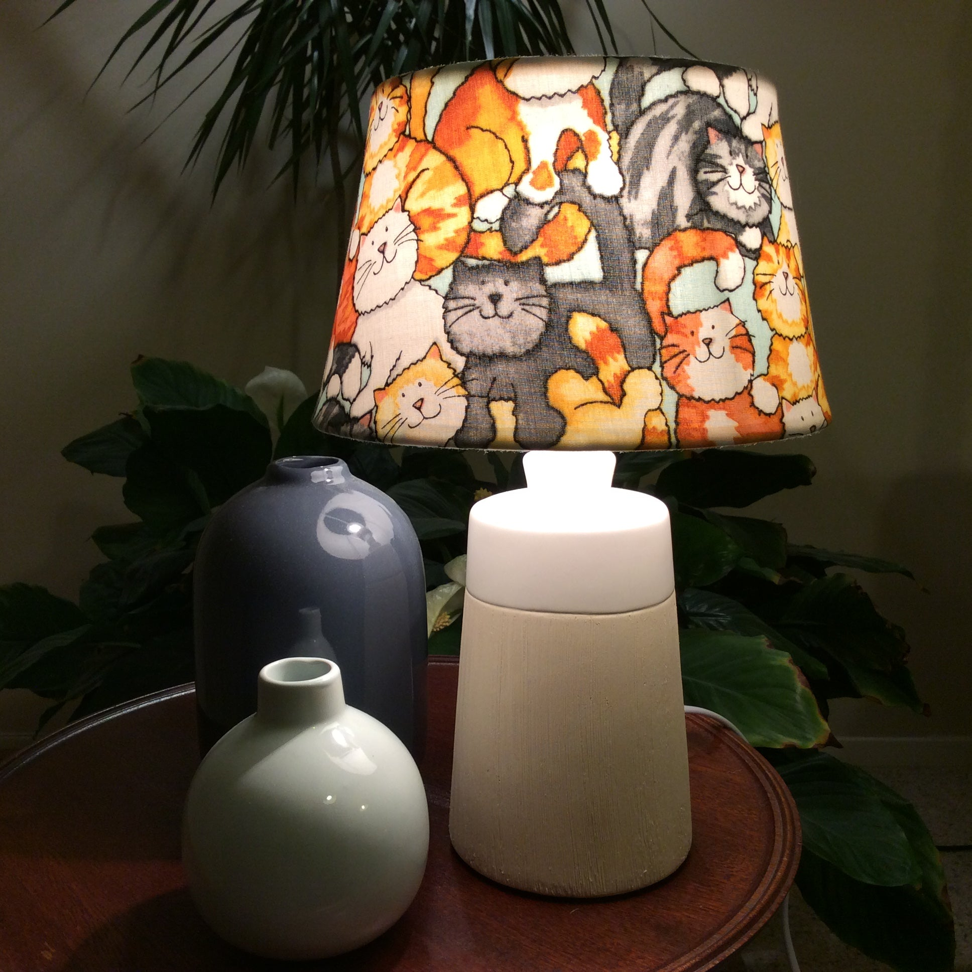 Grey, orange and white cats on a small fabric shade with a small cream and white stand.