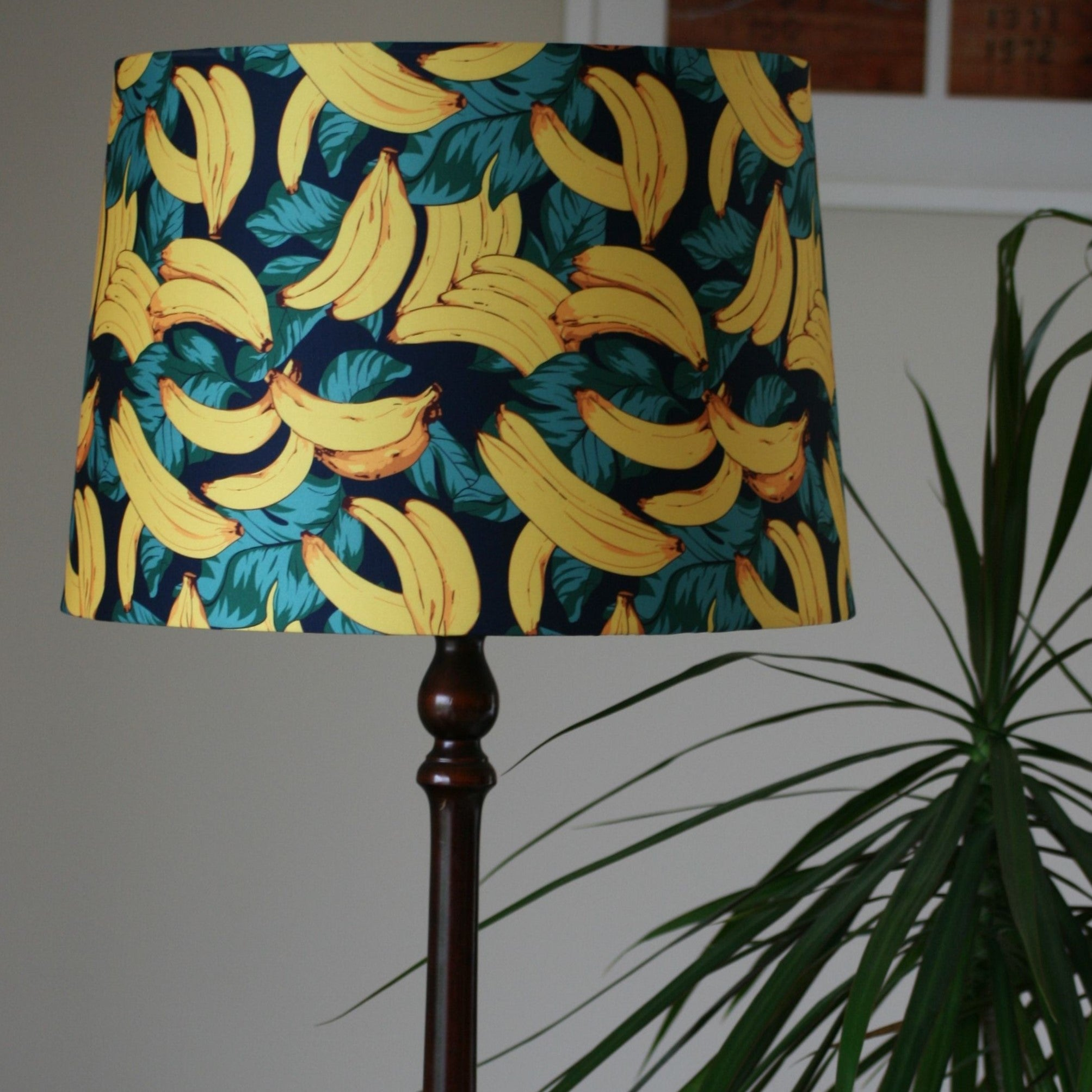 Yellow bananas, greeny blue leaves on a navy background. Large tapered shade on a brown floor stand.