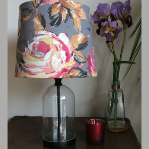 Glass bottle table lamp with grey floral shade