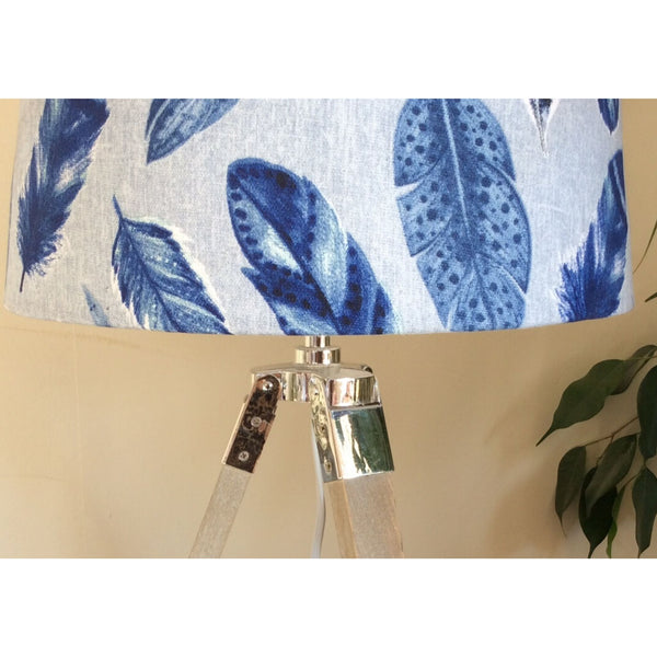 Close up of blue feathers lampshade and tripod stand