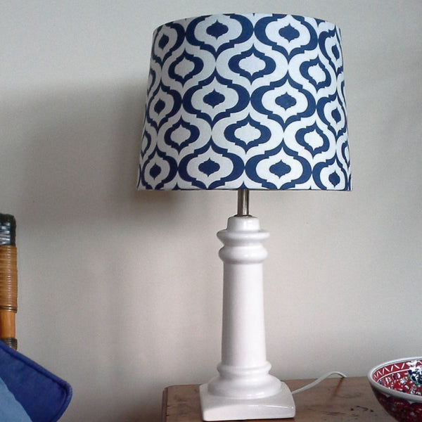 Blue geometric fabric on medium tapered lampshade on a porcelain lamp stand sitting on a wooden side table.