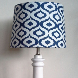 Blue geometric print fabric lampshade on white lampstand