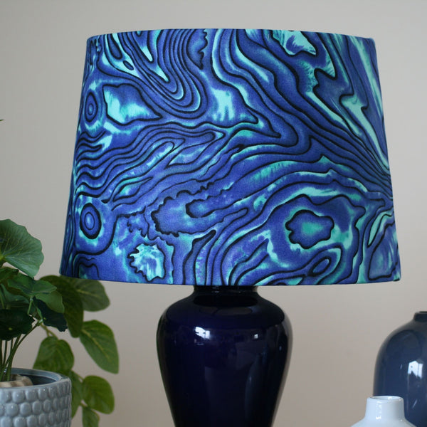 Paua fabric used on a medium tapered shade on a blue ceramic table lamp.