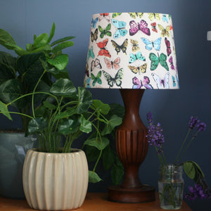 Multicoloured butterflies on a cream fabric made into a small tapered lampshade, on a wooden stand surrounded by plants.