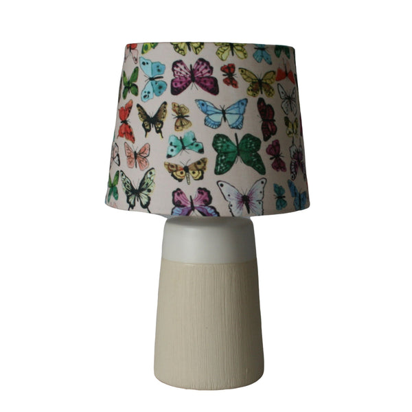 Multicoloured butterflies on a cream fabric made into a small tapered lampshade, on a small cream and white stand.