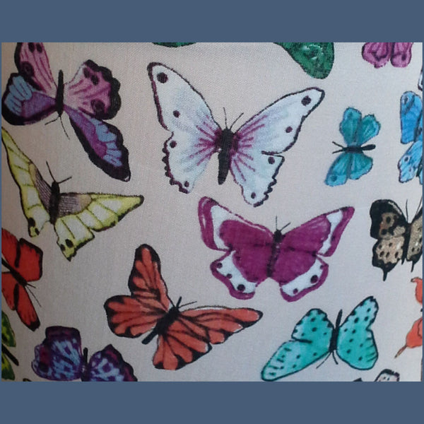 Multicoloured butterflies on cream background close up