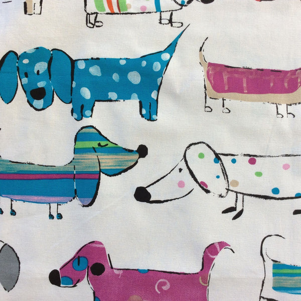 Colourful dogs fabric close up of dogs in blues on a white background.