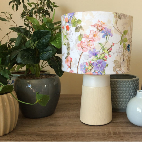 Cottage garden flowers on a small barrel shade and a small cream and white stand.