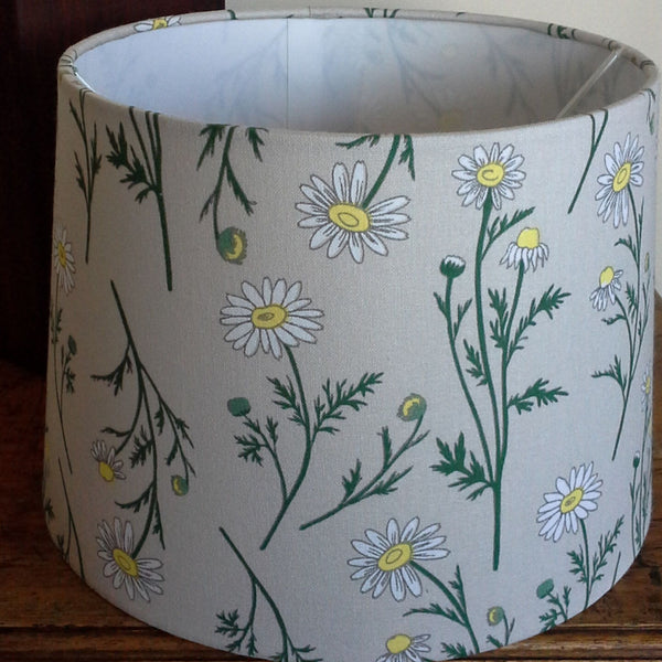 Pattern of daisies with white petals, yellow centres on green stalks and a dove grey background. On a large tapered lampshade.