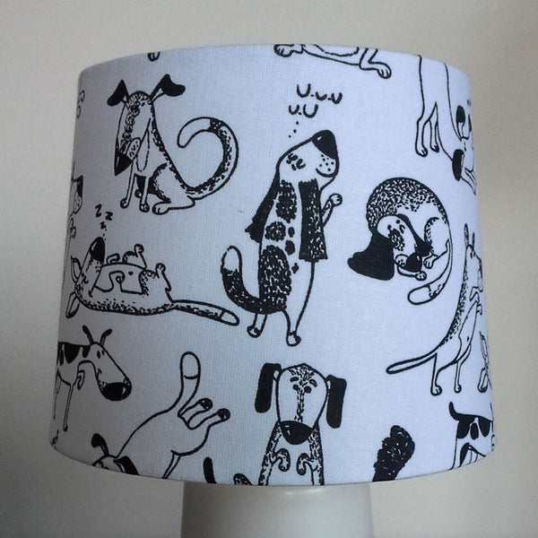 A range of playful dogs etched in black on white background on a small tapered lampshade.