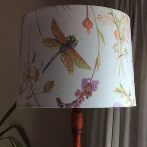 Green, orange and blue dragonfly with purple flower and foliage on large fabric shade.