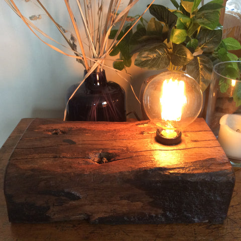Embedded nails in recycled yarrah wharf timber with lit Edison bulb.