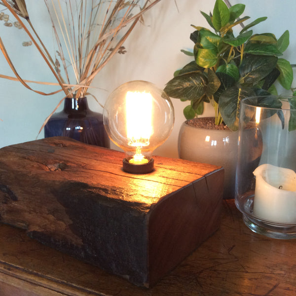 End grain of recycled yarrah wharf timber with lit Edison bulb.