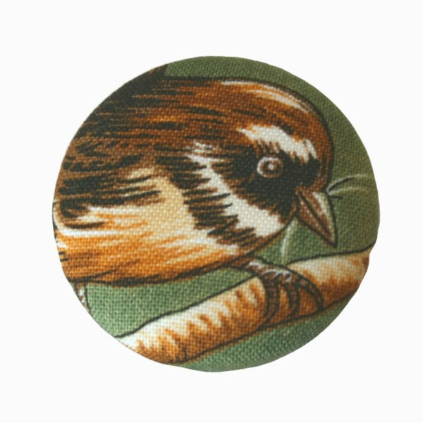 One badge with fantail or pīwakawaka sitting on a branch with an olive green background.