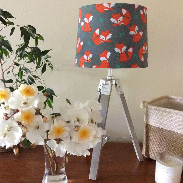 Fox fabric lampshade on wooden tripod stand.