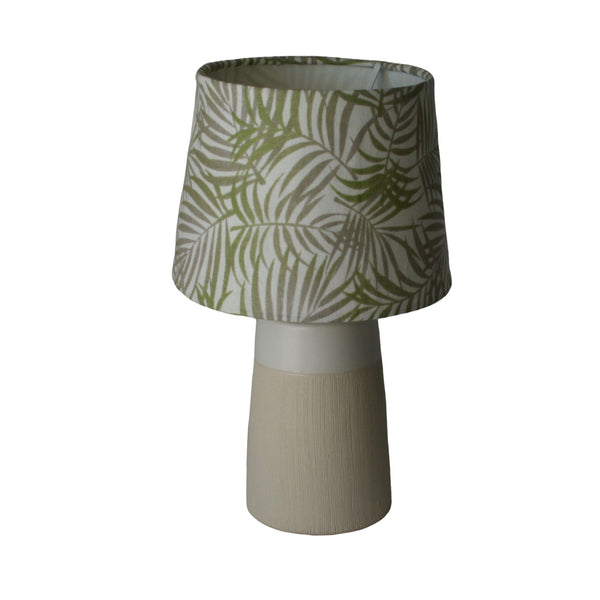 Soft green and grey fern leaves on white background small lampshade on small cream and white lampstand.