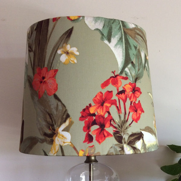 Green frangipani fabric on a medium sized shade on a glass bottle stand with brass fittings.