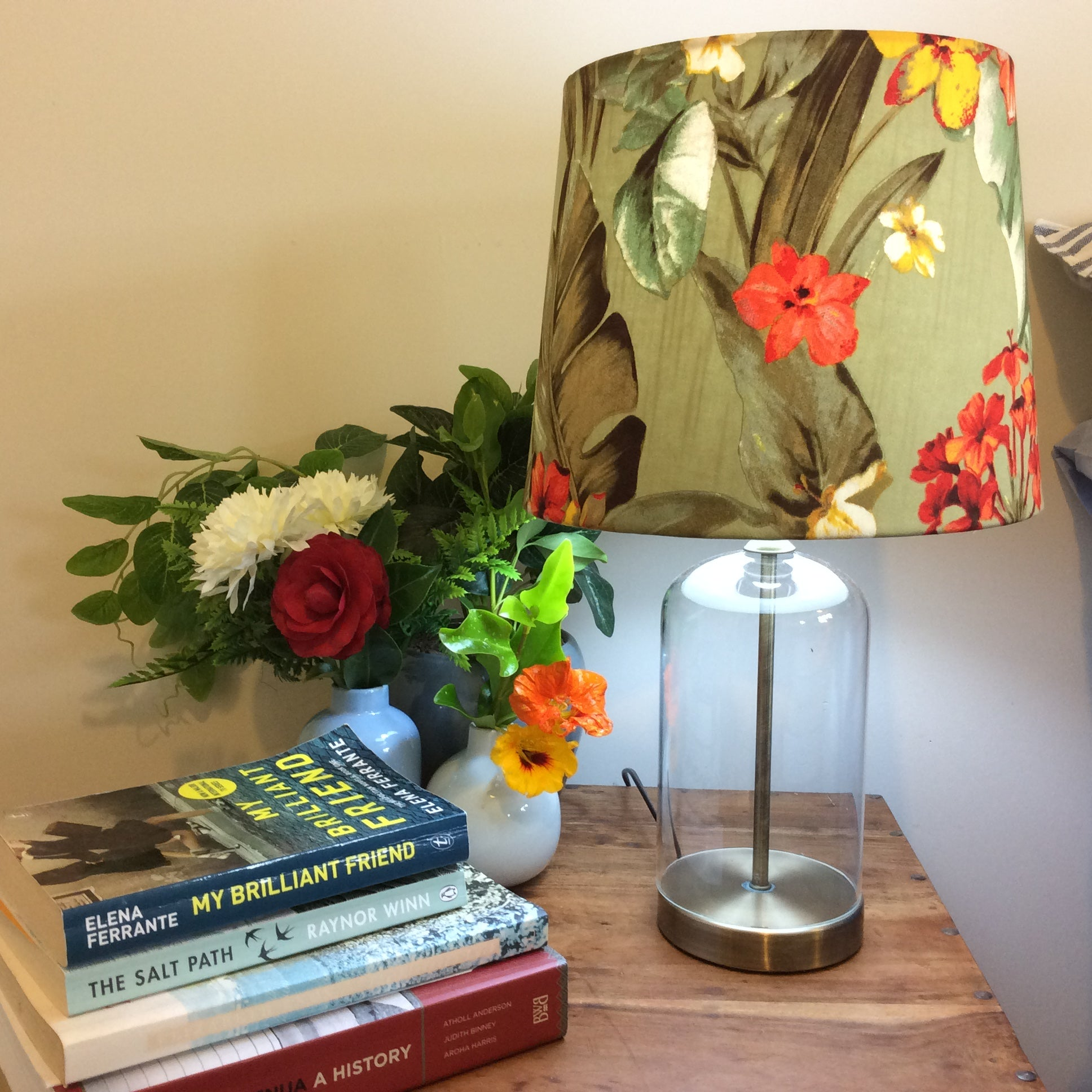 Glass bottle table lamp with green floral shade