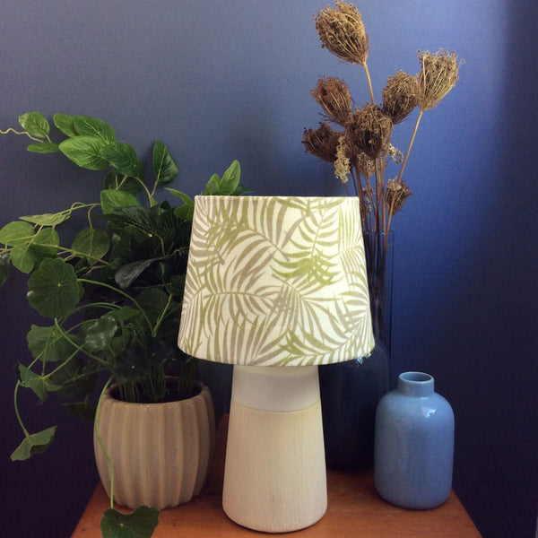 Green grey fern on white fabric shade on small base.