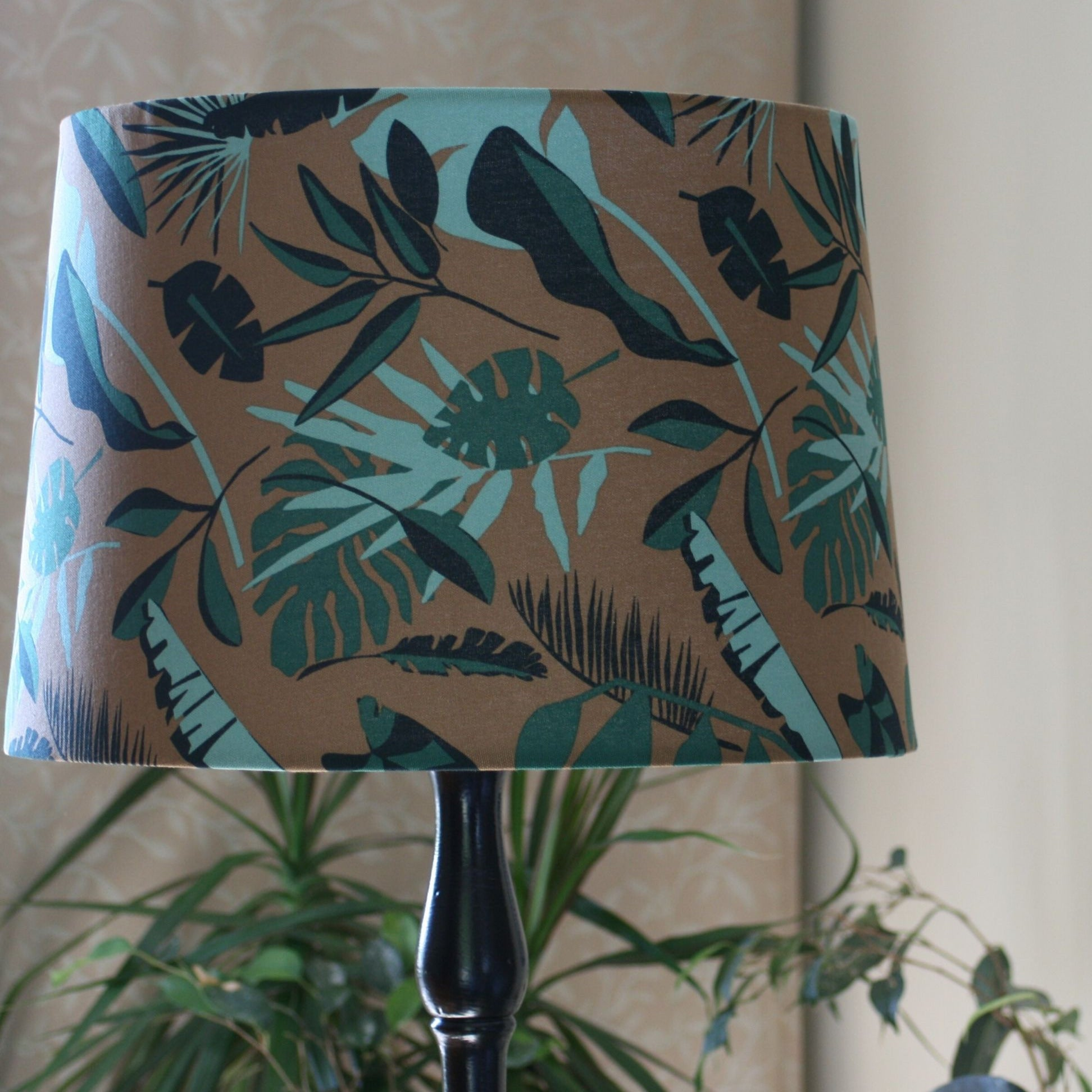 Green leaves and brown khaki fabric made into large tapered shade on a floor stand.