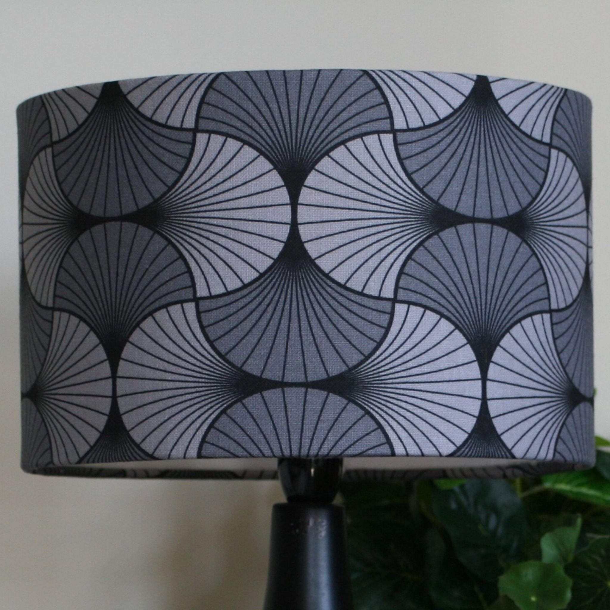 Grey geometric fabric used on a medium drum shade and black stand.